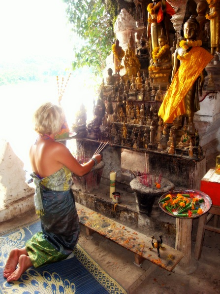 praying in the Buddha cave of Luang Probang